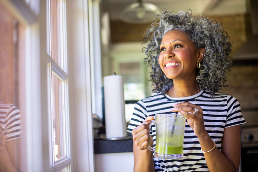 Mature woman with greying curly hair enjoying a smoothy by the window